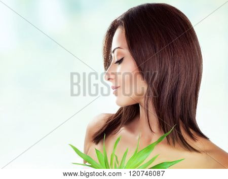 Side view of gentle female with closed eyes posing over blur and white background, holding fresh green leaves, spending day in luxury spa salon