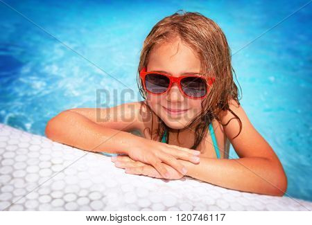 Portrait of cute little girl wearing sunglasses having fun in swimming pool, spending summer vacation on the beach resort