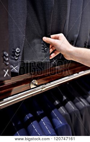 Hand Pick Out Man's Suit Jacket In A Shop