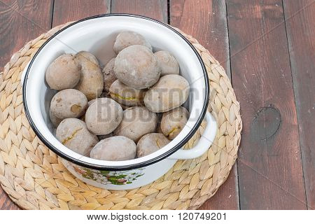 Jacket Potatoes in Cooking Pot on Wooden Background