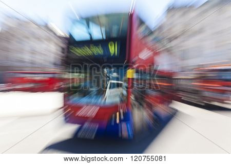 Motion blurred zoomed photograph of a red London double decker bus