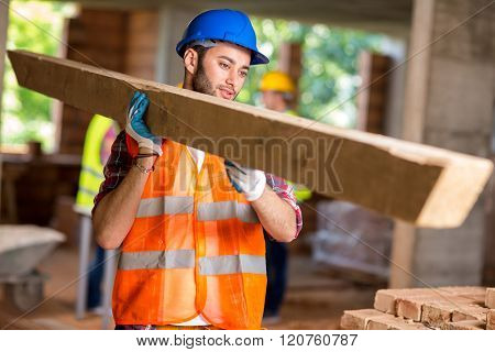 Young worker bring construction timber at work