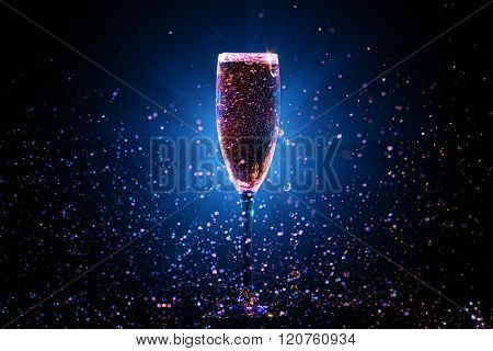 Champagne pouring in glass on black background