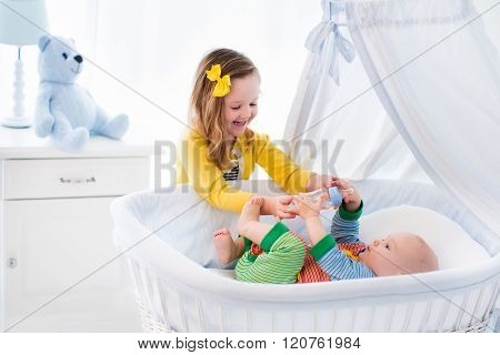 Little Girl Giving Baby Brother Bottle With Milk