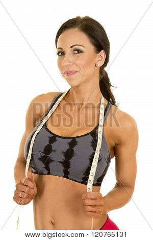 A woman with a smile on her face with her measuring tape around her neck.