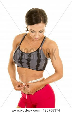 a woman looking down measuring her waist.