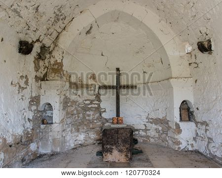 Interior of a deserted orthodox Christian church with a wooden cross and Saint pictures