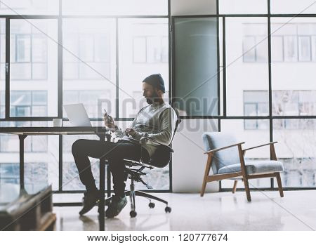 Businessman on modern loft office. Texting message smartphone. Generic design notebook wood table. H