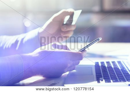 Businessman holding hand credit card and using smartphone.Blurred background, film effect.  Horizontal mockup.