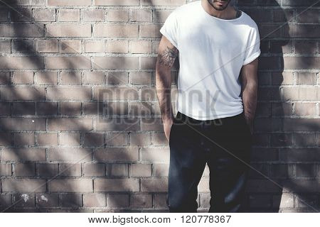 Photo bearded man with tattoo wearing blank white tshirt and black jeans. Bricks wall background. Wi