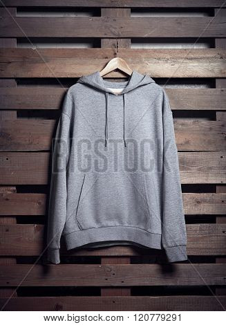 Photo of gray hoody holding on wood background. Vertical blank mockup