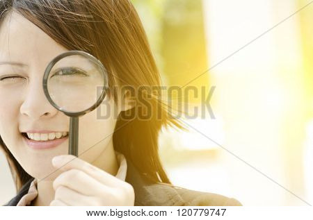 Young Asian business woman looking through magnifying glass, at an office environment, natural golden sunlight at background.
