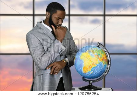 Thoughtful black businessman with globe.