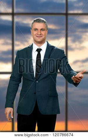 Peaceful mature businessman near window.