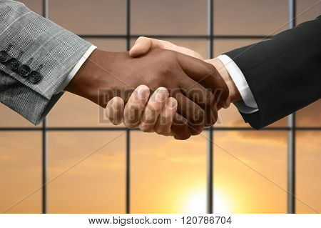 Men shake hands beside window.