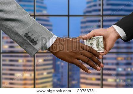 Manager handing money near window.