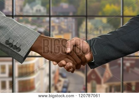 Midday handshake of two businessman.