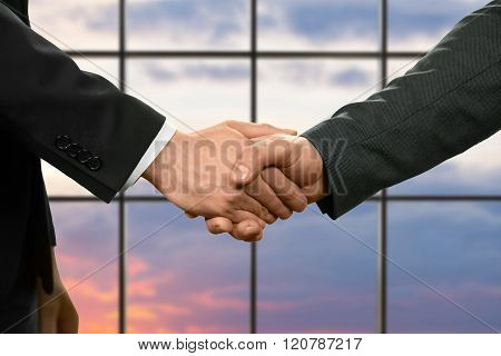Businessman shake hands at sunset.