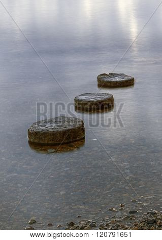 Abstract Of Three Round Objects In Water.