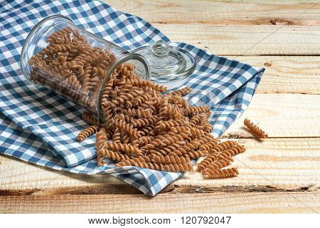 Wholemeal Pasta Falling Out Of A Glass Jar On A Blue Patterned Kitchen Towel On Rustic Wood