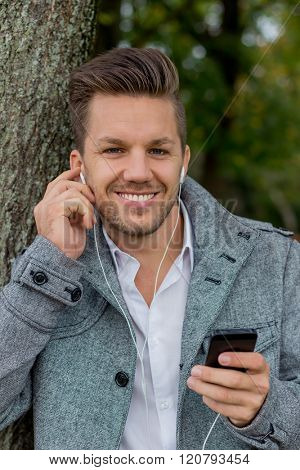 man listens to music on mobile phone