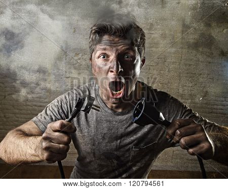 young untrained man joining electrical cable suffering domestic accident with dirty burnt face in funny shock expression screaming crazy in electricity DIY repairs danger concept