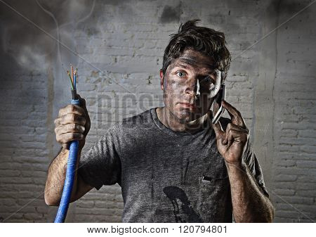 young man holding electrical cable smoking after electrical accident with dirty burnt face in funny desperate expression calling with mobile phone asking for help in electricity DIY repairs danger concept