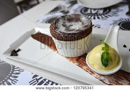 Hot Chocolate Souffle with Vanilla ice cream on a white plate