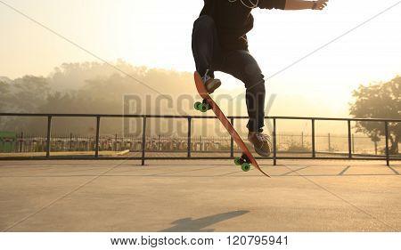 one young skateboarder skateboarding at sunrise skatepark