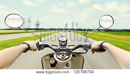 Man driving on scooter on big speed on asphalt road