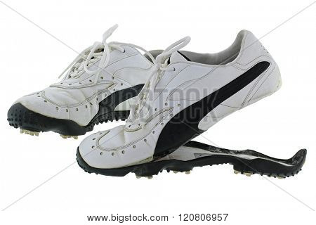 A pair of old and dirty Golf shoes in black and white with split rubber sole, isolated on white