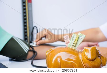 Medical Cost Concept By Cash In Piggy Bank And Doctor Checking Blood Pressure In Background