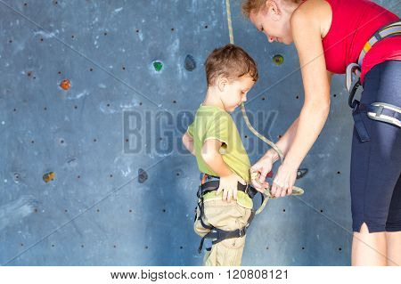Little Boy Climbing A Rock Wall