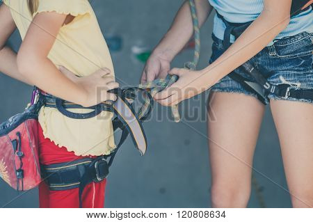 Two Sisters Standing Near A Rock Wall For Climbing