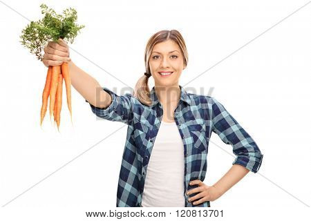 Female agricultural worker holding a bunch of fresh carrots isolated on white background