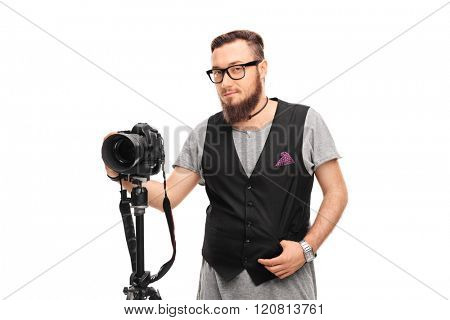 Young male hipster with black glasses and a black vest holding a camera isolated on white background