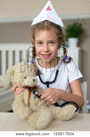 Cute little girl playing in doctor with her toy.