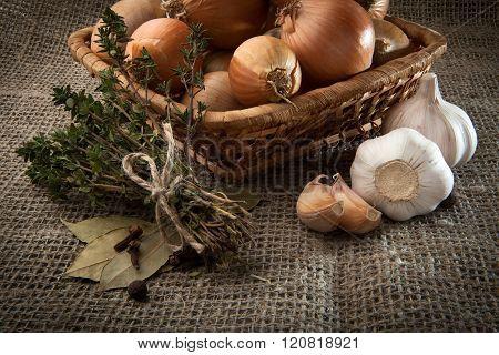 Bulb Onion, Garlik, Sheaf Thyme, Bay Leaf In A Wicker Basket Which Stands On Burlap