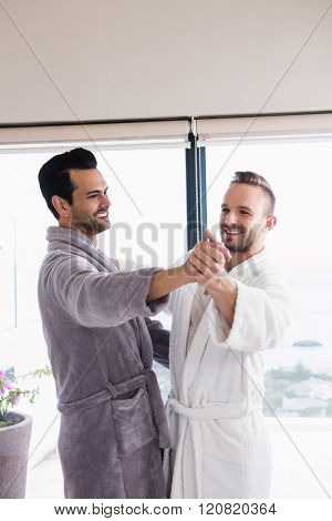 Happy gay couple dancing waltz in bathrobe in bedroom