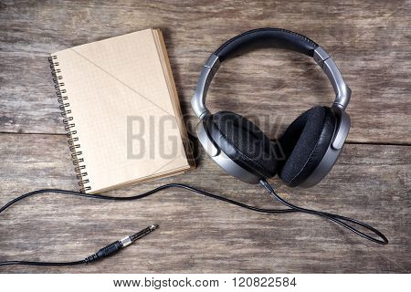 Vintage Headphones and paper note on wooden background