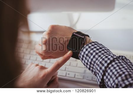 Over the shoulder view of businesswoman using her smart watch at her desk in office