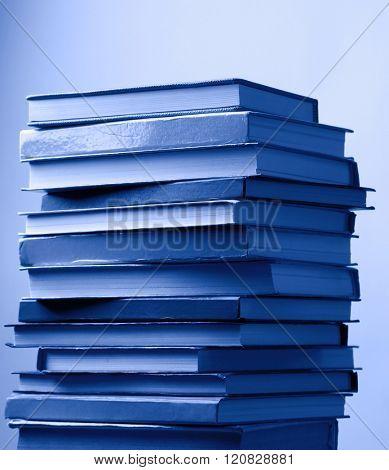 Stack of blue books on light blue background