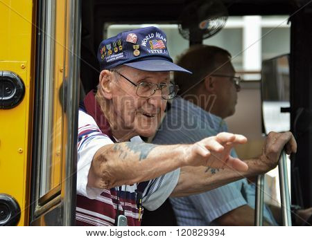 Bangor, Maine/USA-July 4: A WWII Veteran at the 4th of July Parade in 2015 on Main St. in Bangor, Maine proudly waves to the crowd from a bus.