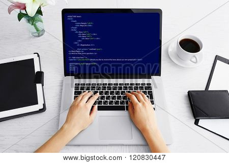 Woman using laptop, writing programming code on laptop
