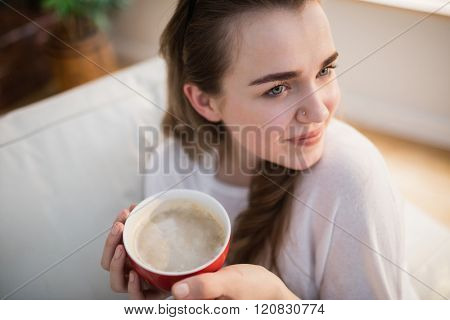 Pretty woman relaxing on couch with coffee in the living room
