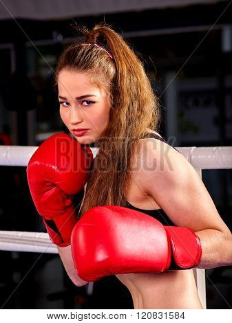 Portrait of sport girl with long hair boxing wearing red gloves.