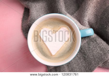 Cup of hot cappuccino with heart marshmallow and warm scarf on pink background, close up