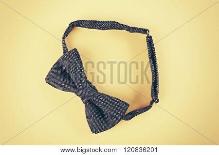 Dark blue bow tie on beige background