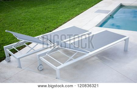 Deck chair by the pool on a sunny day