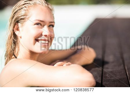 Smiling blonde leaning on pools edge and looking up